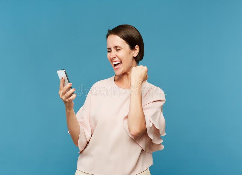 Hembra extática joven que mira la pantalla del smartphone foto de archivo libre de regalías