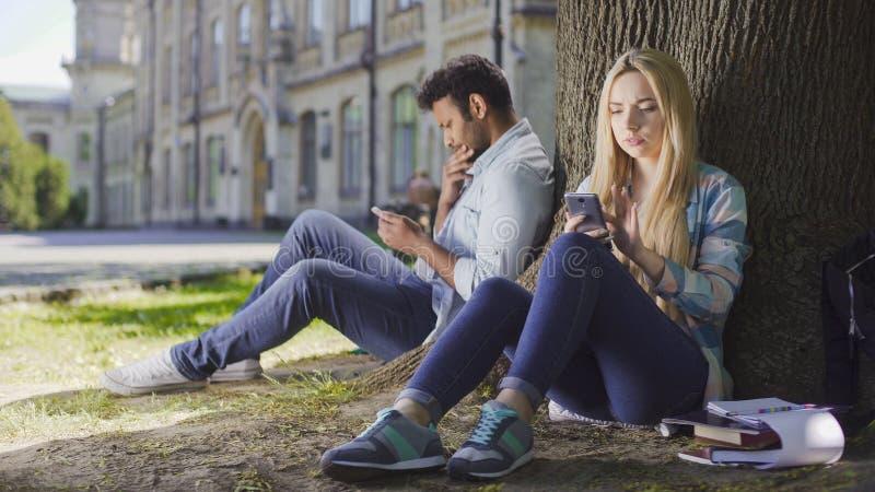 Hembra, extranjeros masculinos que se sientan debajo de árbol, usando el teléfono móvil, muchacha que parece preocupada imágenes de archivo libres de regalías