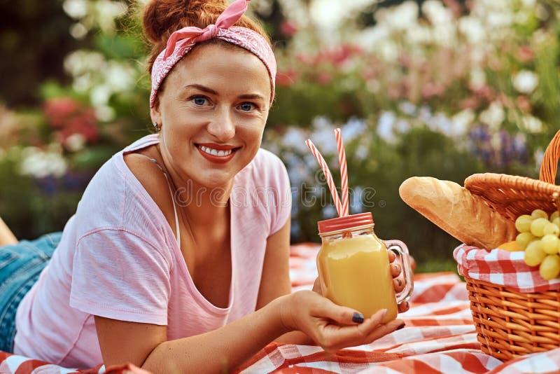 Hembra feliz de la Edad Media del pelirrojo en ropa casual con una venda que goza durante comida campestre al aire libre mientras imagenes de archivo