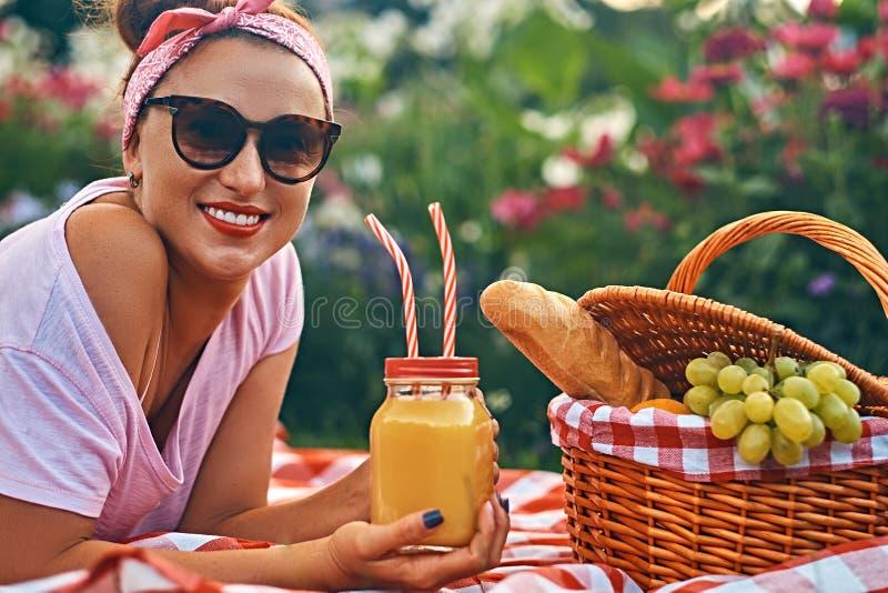 Hembra feliz de la Edad Media del pelirrojo en ropa casual con una venda y las gafas de sol que goza durante comida campestre al  fotografía de archivo libre de regalías