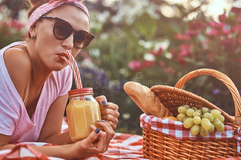 Hembra feliz de la Edad Media del pelirrojo en ropa casual con una venda y las gafas de sol que goza durante comida campestre al  imagen de archivo libre de regalías
