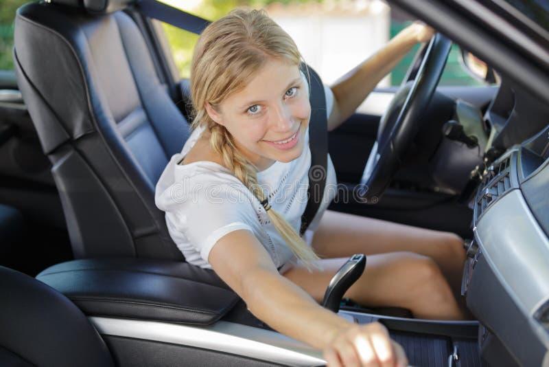 Hembra feliz joven en coche fotografía de archivo