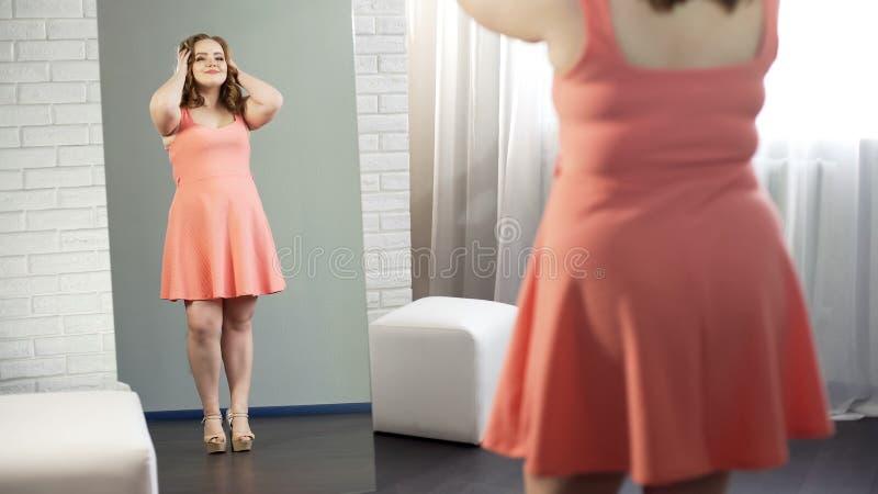 Hembra gorda alegre en vestido que admira su reflexión de espejo, gozando siendo regordete imagen de archivo libre de regalías