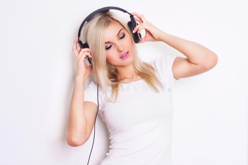 Hembra hermosa del baile en auriculares mientras que escucha la música sobre el fondo blanco. fotografía de archivo
