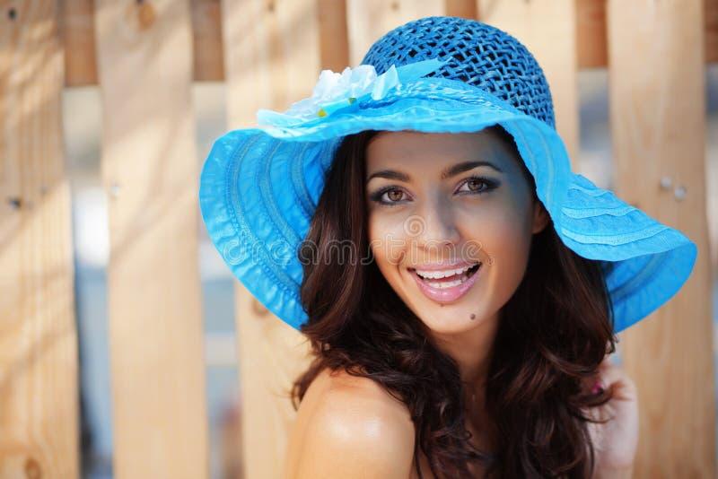 Hembra hermosa en el sombrero de la señora azul imagenes de archivo