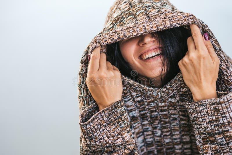 Hembra hermosa feliz que lleva y que juega con el suéter acogedor que presenta contra el lago El retrato de la hembra sonriente s imagen de archivo libre de regalías