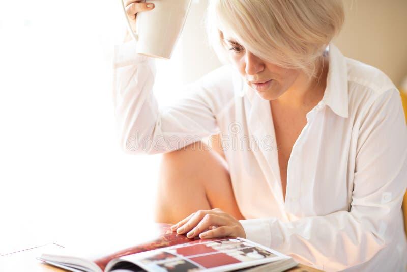 Hembra hermosa joven que lee un libro que sostiene una taza El espacio hermoso por la ventana se encendió con luz del sol imagen de archivo libre de regalías