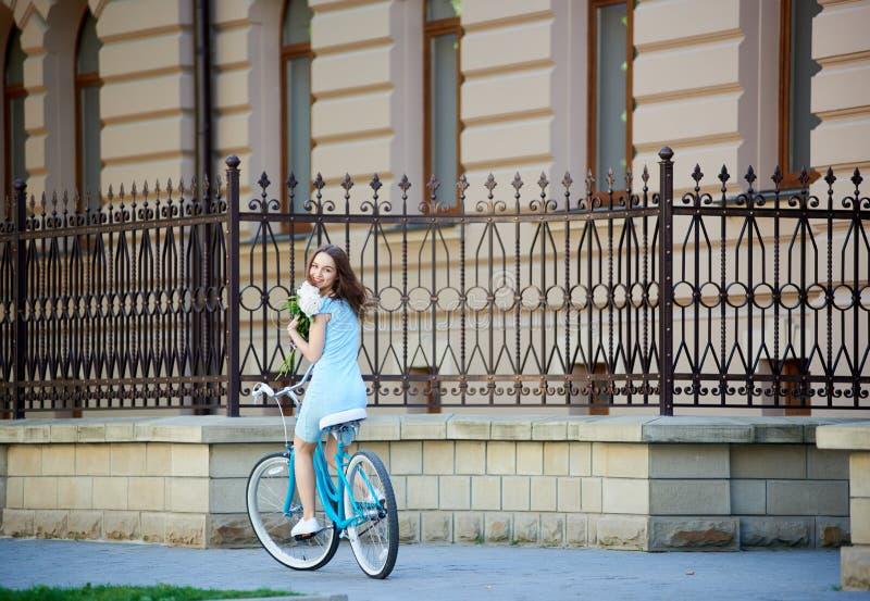 Hembra hermosa sonriente que mira detrás mientras que sujeta las flores y monta la ciudad bastante histórica azul de la bicicleta foto de archivo libre de regalías