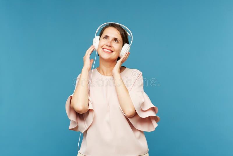 Hembra joven alegre que disfruta de su música preferida en auriculares imágenes de archivo libres de regalías