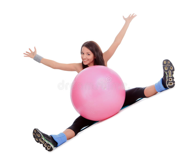 Hembra joven atractiva con la bola de la aptitud en centro de deporte foto de archivo