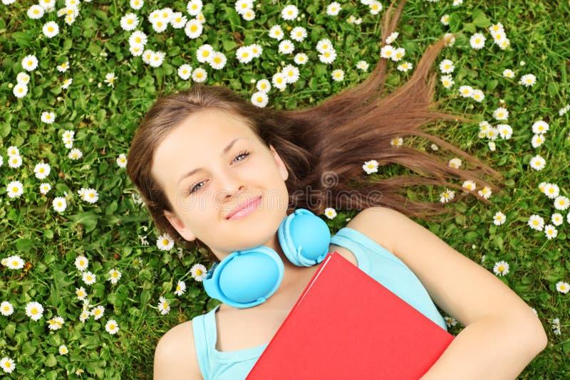 Hembra joven con el libro y los auriculares que mienten en una hierba con flujo imágenes de archivo libres de regalías