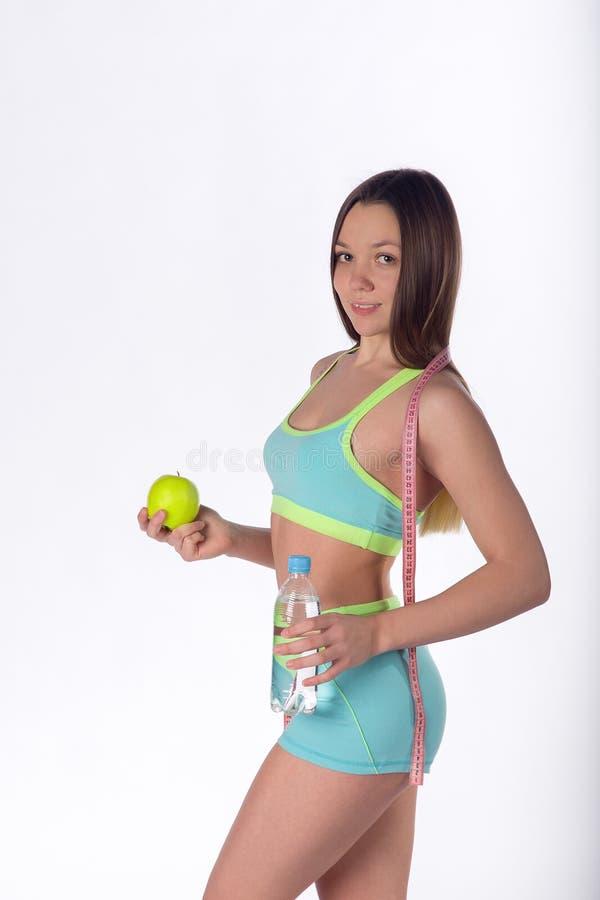 Hembra joven con la manzana, botella de agua y cinta métrica imagen de archivo