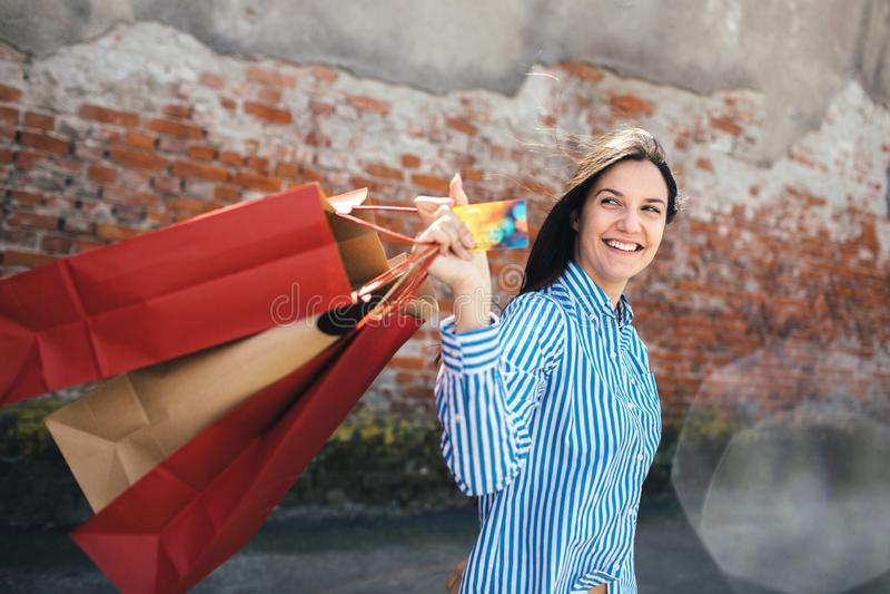 Hembra joven con los bolsos de compras en la calle imagen de archivo libre de regalías