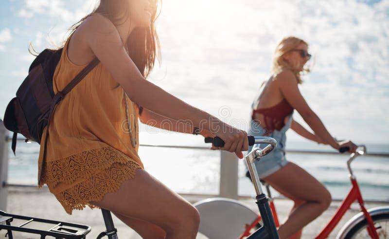 Hembra joven dos que completa un ciclo al aire libre en un día soleado imagenes de archivo