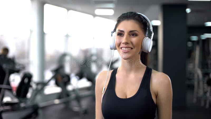 Hembra joven en gimnasio que escucha la música, motivación de los deportes, forma de vida activa fotografía de archivo libre de regalías