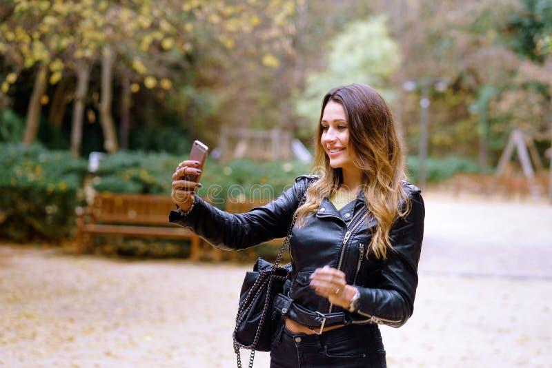Hembra joven encantadora en equipo de moda que sonríe y que toma el selfie imagenes de archivo