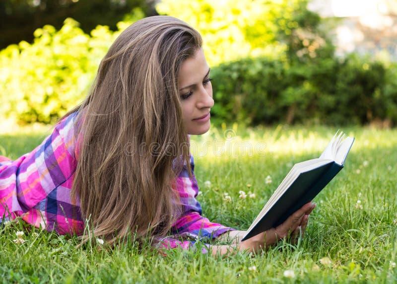 Hembra joven hermosa que lee un libro foto de archivo libre de regalías