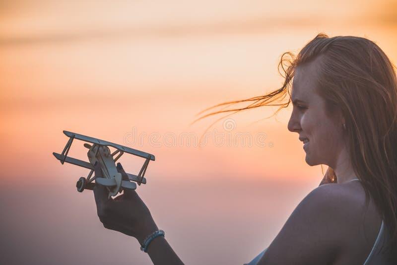 Hembra joven hermosa que sostiene el pequeño aeroplano de madera retro al aire libre foto de archivo libre de regalías