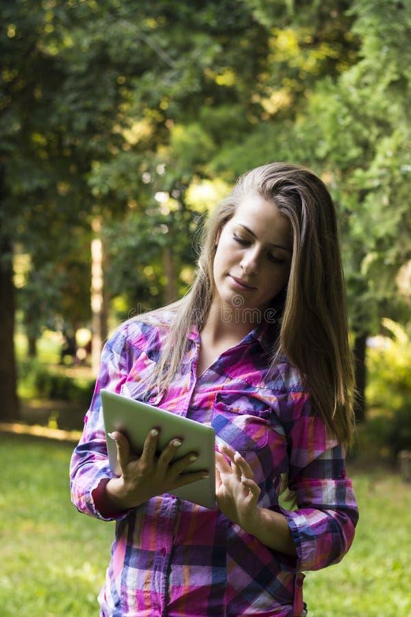 Hembra joven hermosa que usa la tableta digital fotografía de archivo