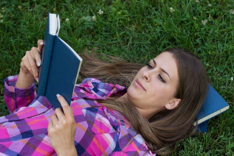 Hembra joven que lee un libro foto de archivo