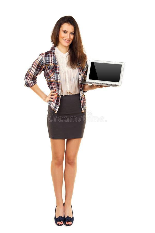 Hembra joven que muestra la pantalla en blanco de un ordenador portátil fotos de archivo