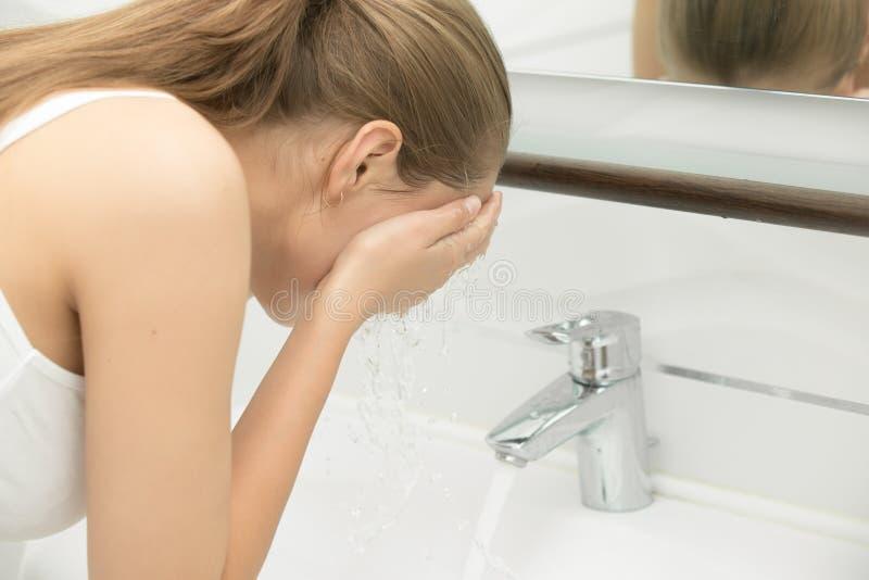 Hembra joven que se lava la cara con agua del claro del golpecito cerca del fregadero foto de archivo