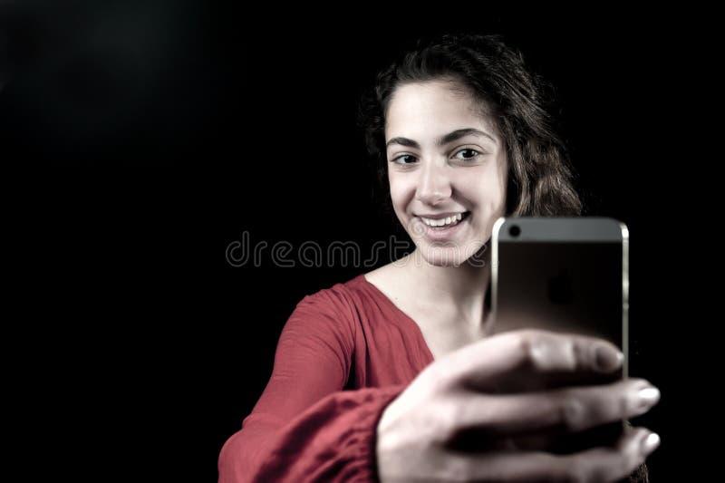 Hembra joven que sostiene un smartphone imagen de archivo