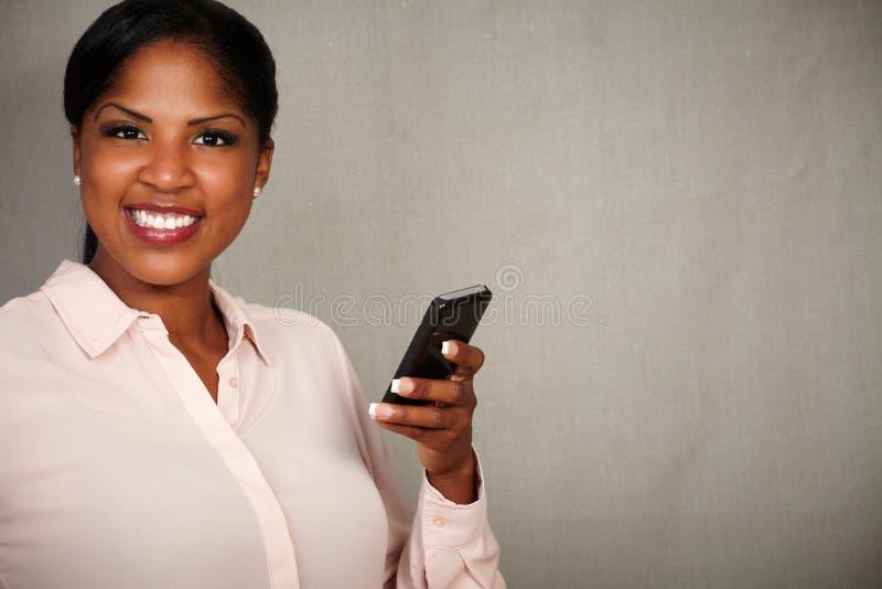 Hembra joven que sostiene un teléfono móvil mientras que sonríe imagenes de archivo