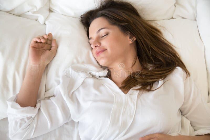 Hembra joven relajada que duerme bien en cama blanca acogedora imagen de archivo