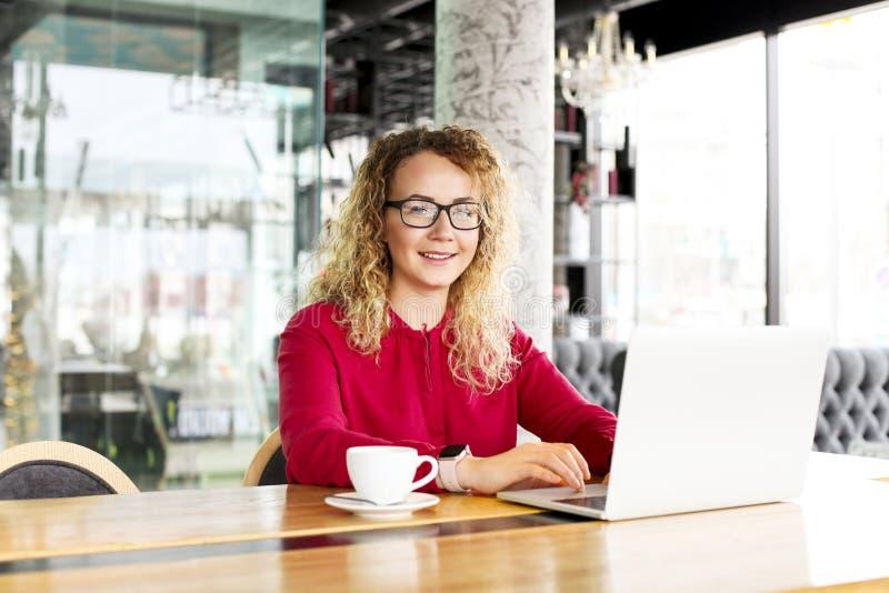 Hembra joven rubia hermosa feliz del pelo rizado en la cafetería usando el ordenador portátil, sonriendo Gla que lleva del freela fotos de archivo