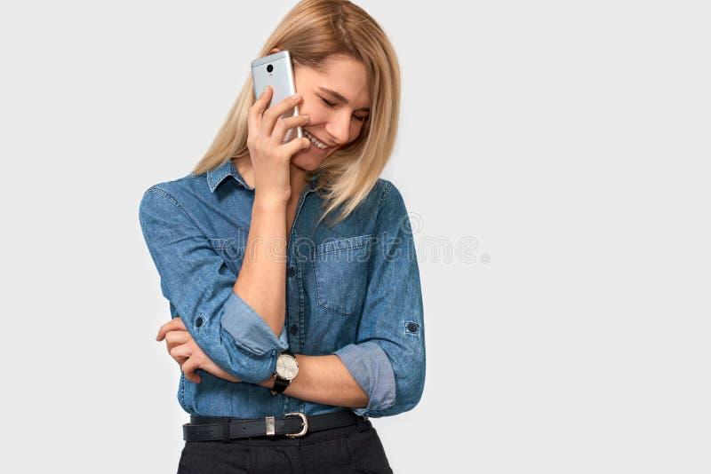 Hembra joven rubia hermosa que habla en el teléfono celular con su novio, pareciendo alegre y feliz en el fondo blanco del estudi fotografía de archivo