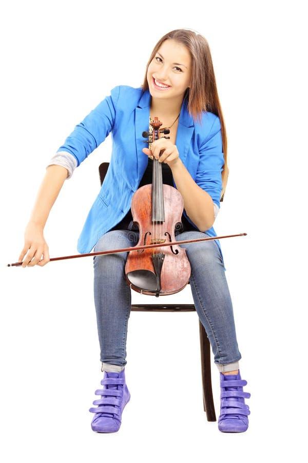 Hembra joven sonriente asentada en una silla de madera que toca el violín fotos de archivo libres de regalías