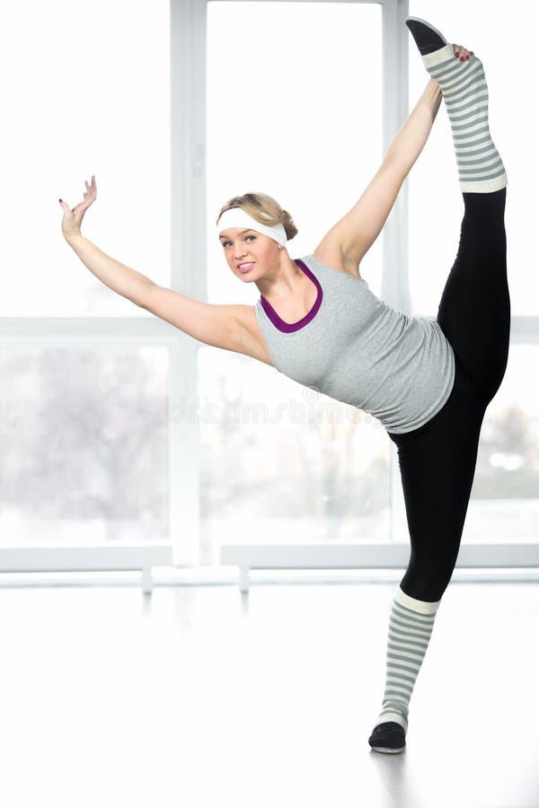 Hembra joven sonriente del bailarín que hace estirando ejercicios fotografía de archivo libre de regalías