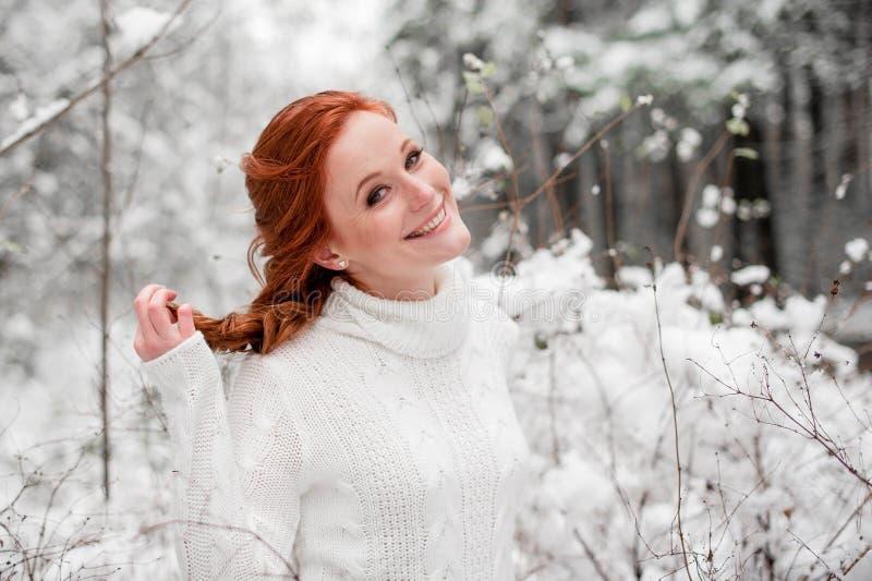 Hembra linda del jengibre en el suéter blanco en la nieve diciembre del bosque del invierno en parque Retrato Tiempo lindo de la  foto de archivo
