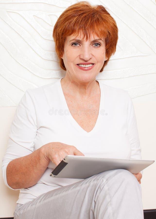 Hembra madura con la tableta digital en casa foto de archivo