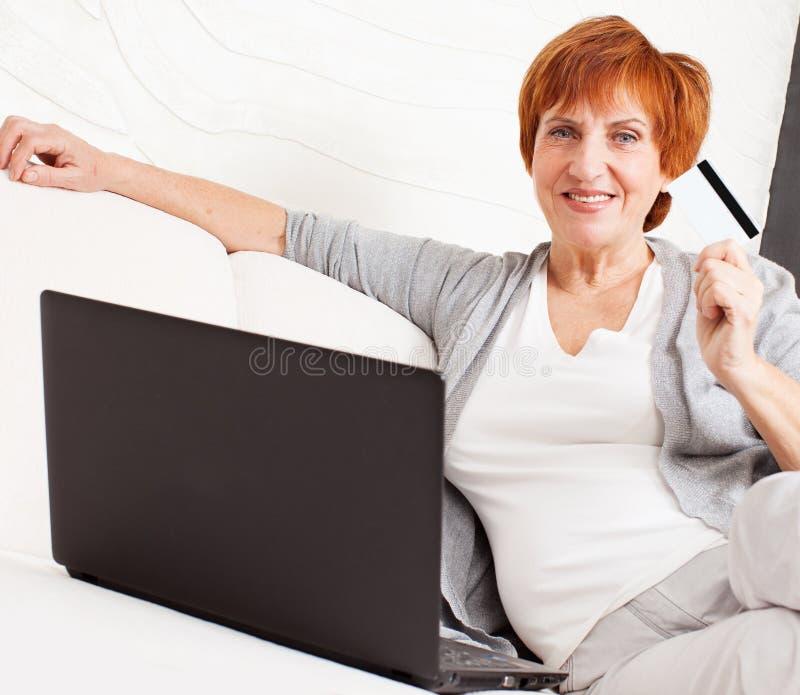 Hembra madura con la tarjeta de crédito y el ordenador portátil fotos de archivo libres de regalías
