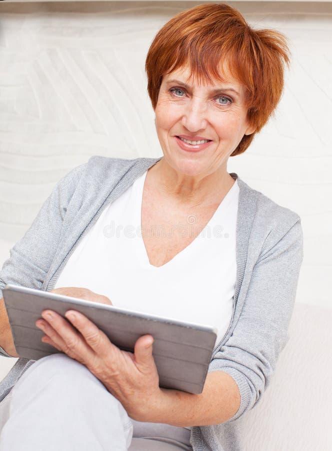 Hembra madura con PC de la tableta fotografía de archivo