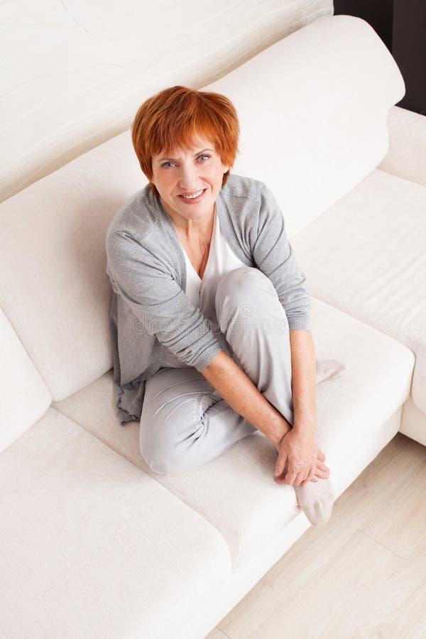 Hembra madura feliz en el sofá imagen de archivo