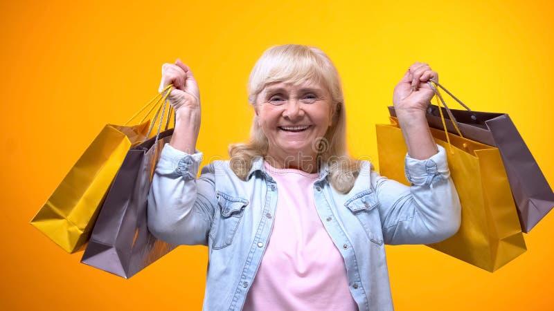 Hembra mayor alegre que sostiene los bolsos de compras, tiempo libre agradable, anuncio fotografía de archivo libre de regalías
