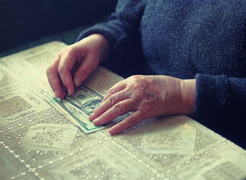 Hembra mayor del latino con la pequeña cantidad de dinero, imagen entonada, foco colorized, selectivo, dof muy bajo fotos de archivo
