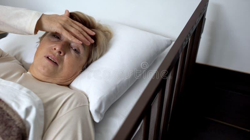 Hembra mayor trastornada que miente en cama de hospital, tocando la frente, jaqueca sufridora imagen de archivo