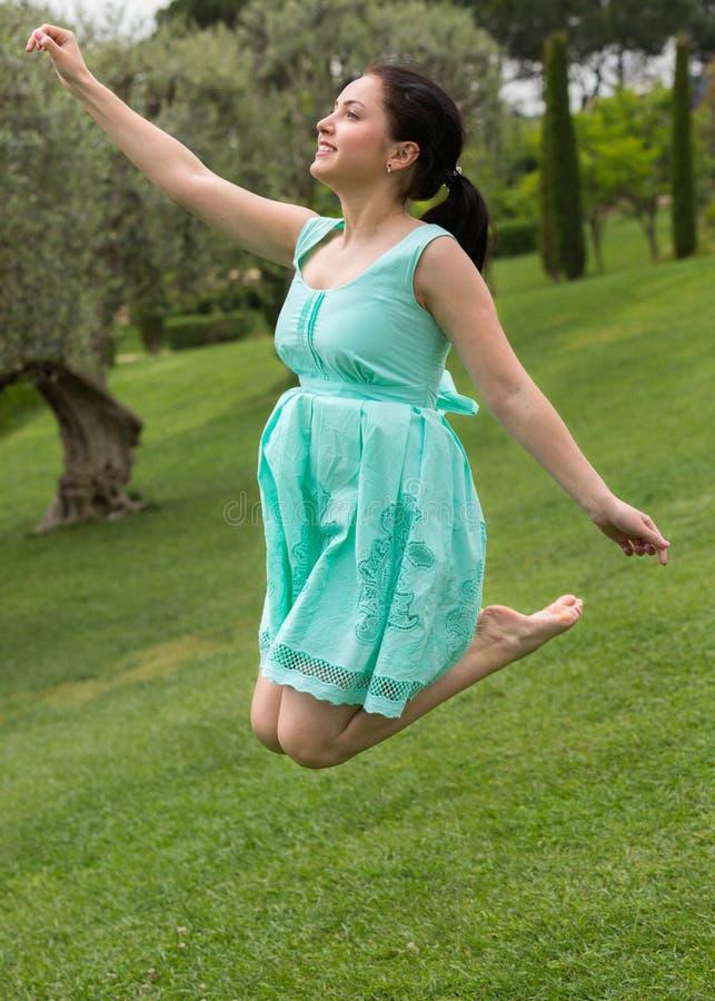 Hembra morena joven en el vestido que salta en el parque foto de archivo libre de regalías