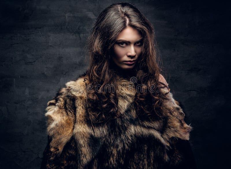 Hembra morena sensual vestida en un abrigo de pieles imagen de archivo