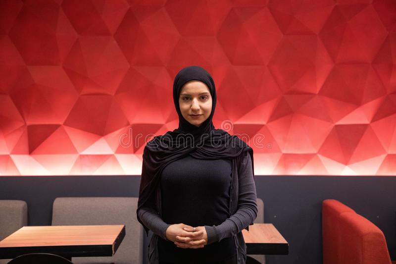 Hembra musulm?n atractiva en un hijab negro que mira la c?mara con el fondo fresco rojo imagen de archivo