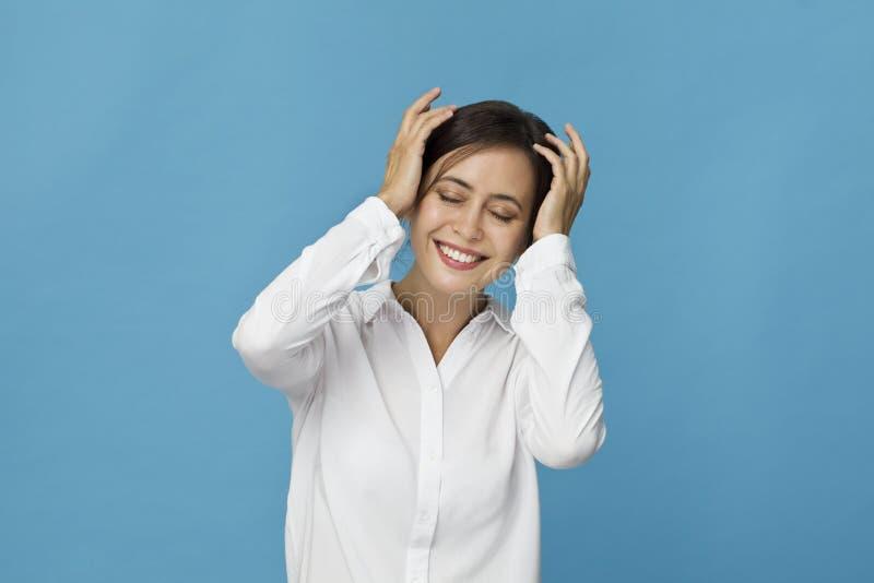 Hembra positiva sonriente con mirada atractiva, camiseta blanca que lleva, presentando contra la pared en blanco azul foto de archivo