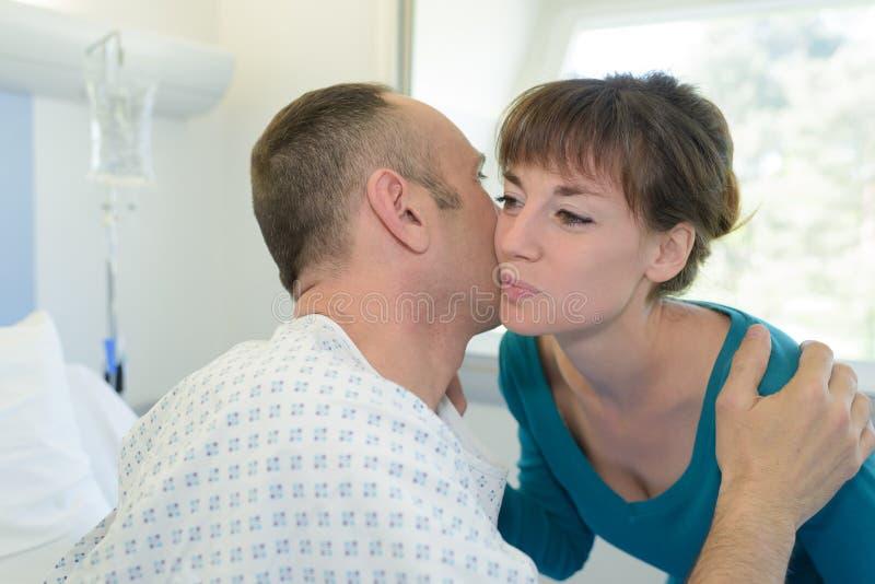 Hembra que besa al paciente enfermo en hospital imagenes de archivo