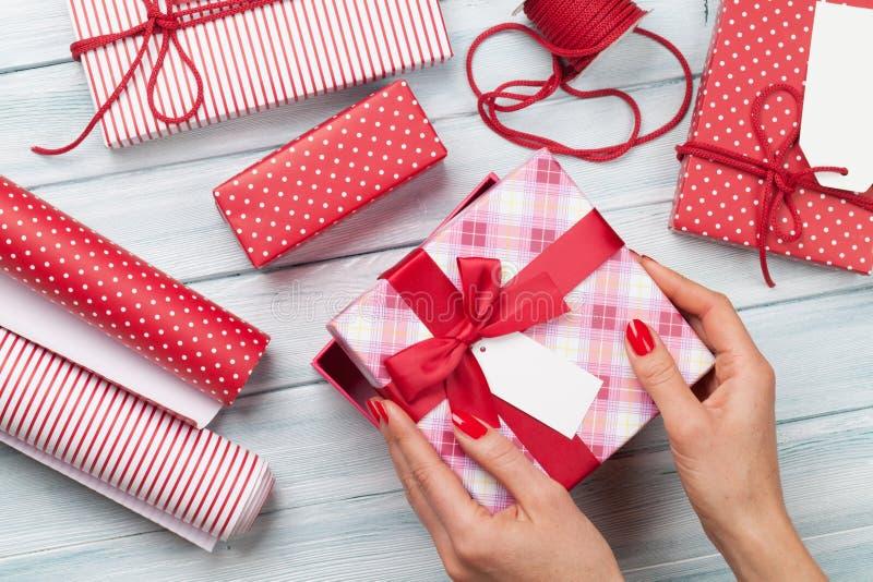 Hembra que envuelve los regalos de la Navidad imagenes de archivo
