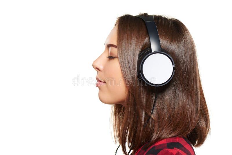 Hembra que escucha disfrutando de música en auriculares con los ojos cerrados imagen de archivo