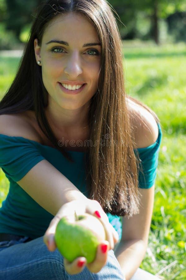 Hembra que sostiene una manzana verde fresca foto de archivo libre de regalías
