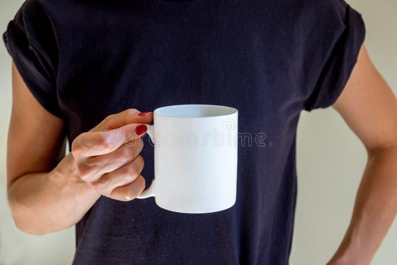 Hembra que sostiene una taza de café, fotografía común diseñada de la maqueta fotografía de archivo libre de regalías